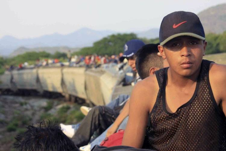 "Young Central American migrants ride atop the northbound freight train called  ""La Bestia"" on their journey through Mexico toward the United States. Mexican activist and photographer Irineo Mujica was one of the first to publish photo documentation of this migrant route, fraught with run-ins with organized crime."